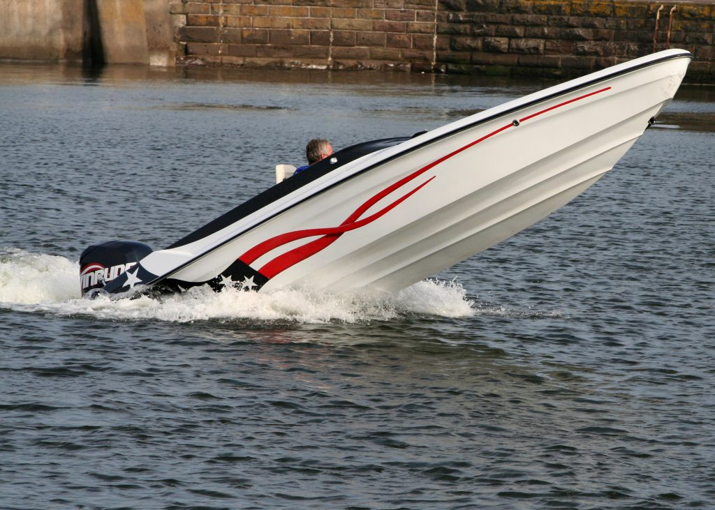 speed boat with its nose out of the water, exposing the bottom of the boat above the water