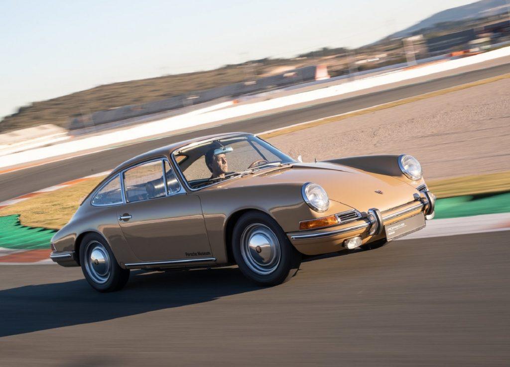 A tan 1964 Porsche 911 2.0 drives on a racetrack