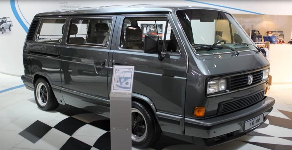A charcoal colored 1985 Porsche B32 Minivan is on display in a museum.