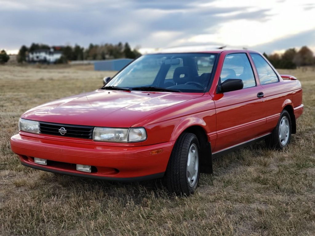 A red 1991 Nissan Sentra SE-R in a field