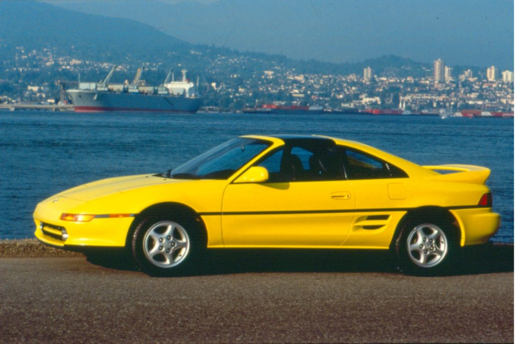 The side view of a yellow 1992 Toyota MR2 by a harbor