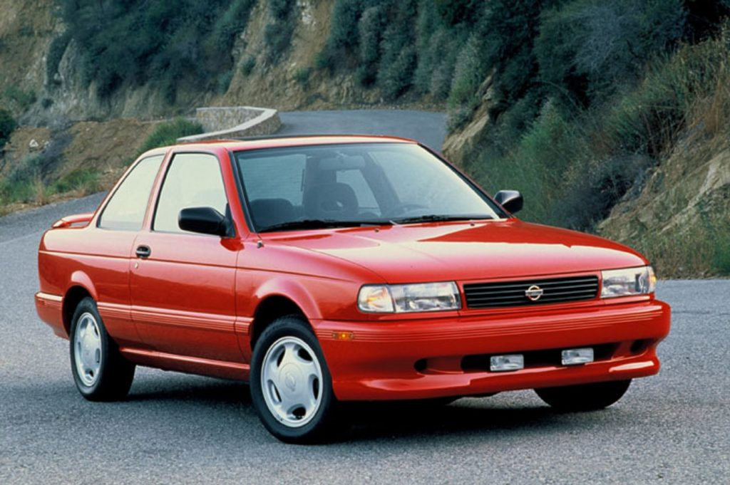 A red 1994 Nissan Sentra SE-R parked on a mountain road