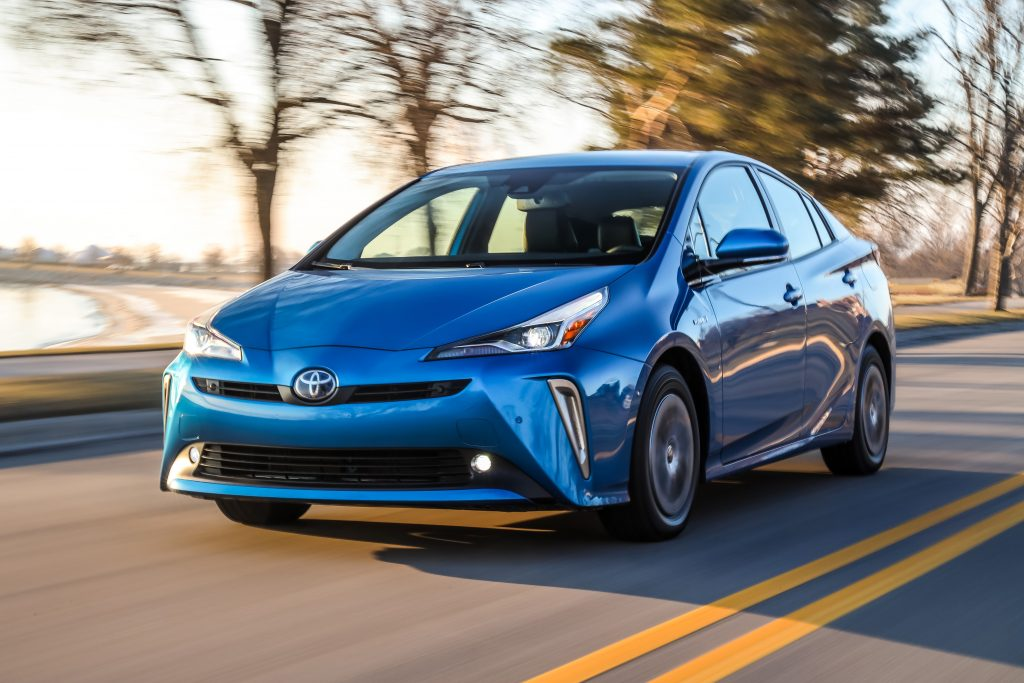 blue Toyota Prius at speed on a lakeside road