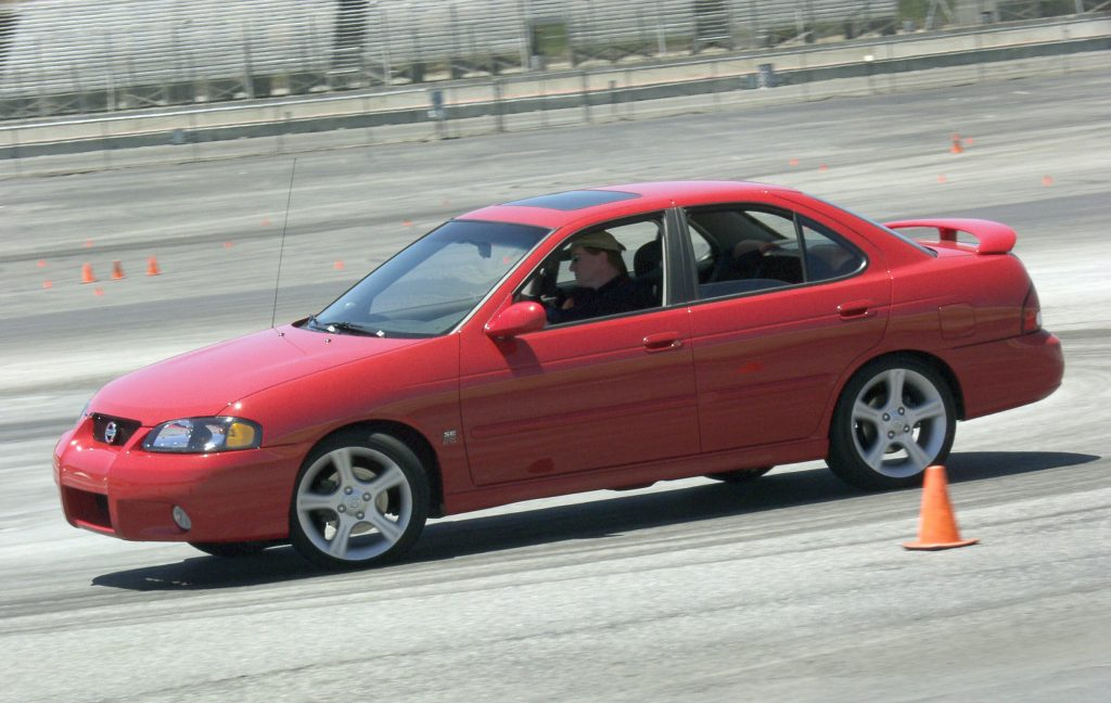 A red 2002 Nissan Sentra SE-R drives on an autocross course
