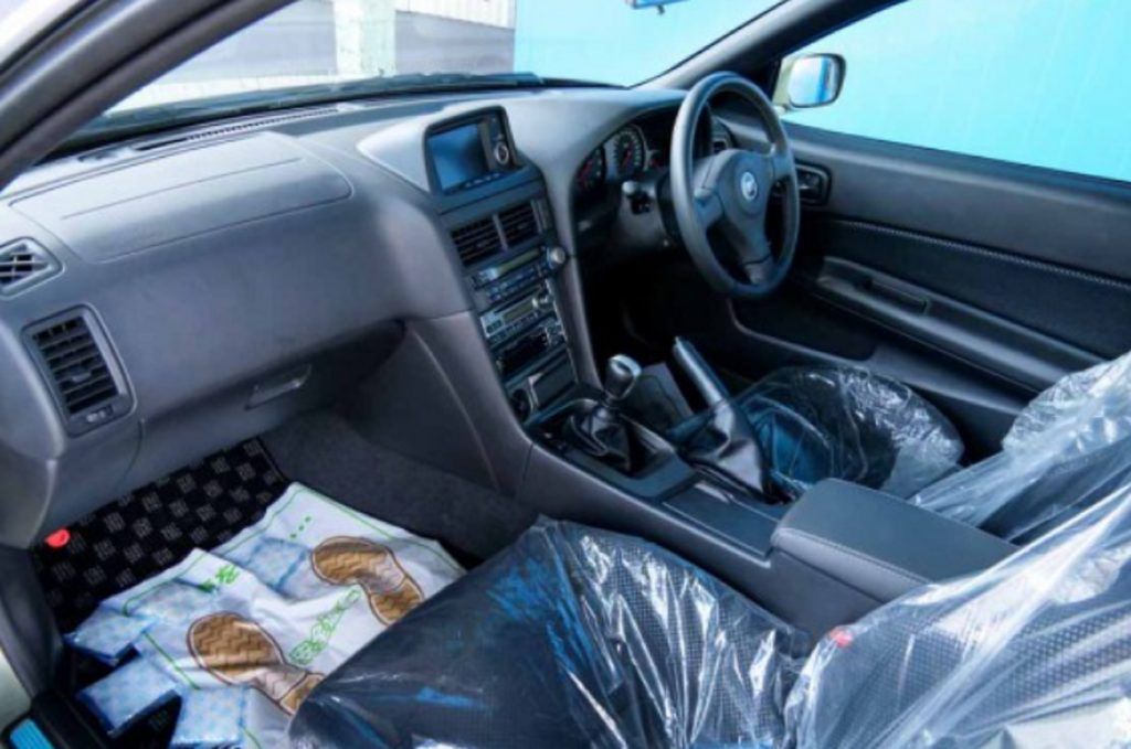 The plastic-wrapped front seats and black dashboard of a 2002 R34 Nissan Skyline GT-R V-Spec II Nur