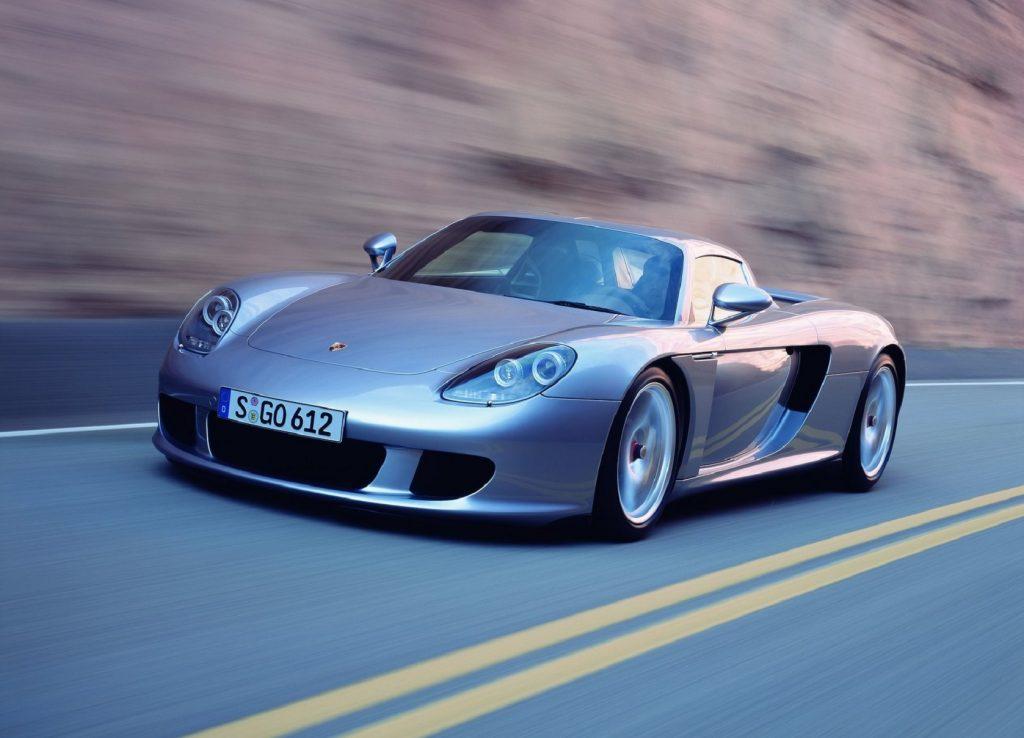 A silver 2004 Porsche Carrera GT drives through a canyon