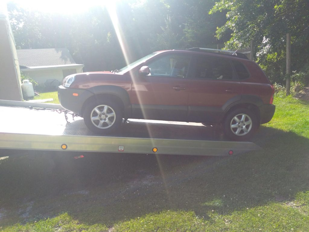 A burgundy 2005 Hyundai Tucson is loaded on a flat-bed tow truck