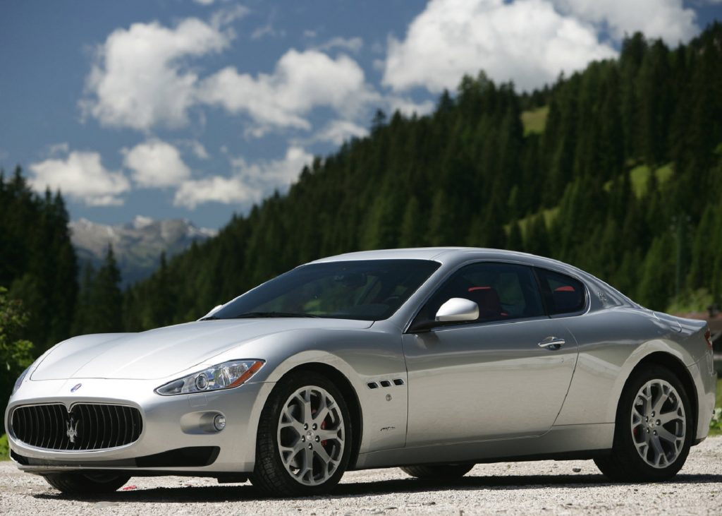 A silver 2008 Maserati GranTurismo in front of a forested mountain