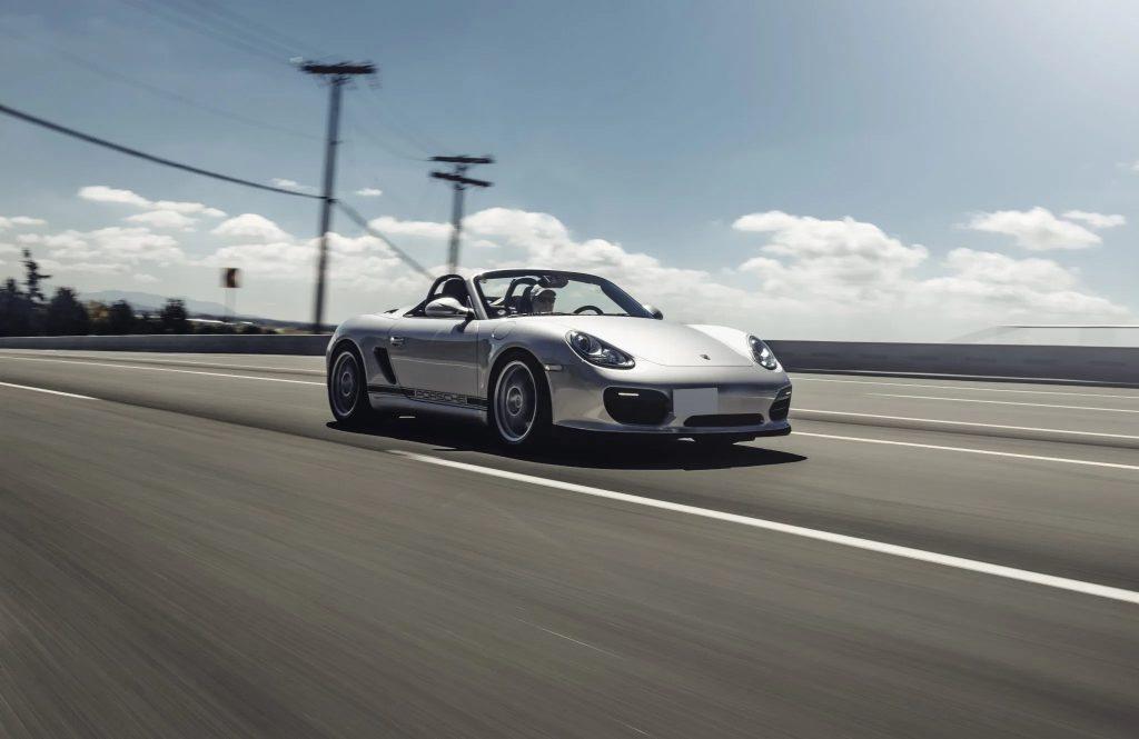 A silver 2011 Porsche Boxster Spyder drives down the road