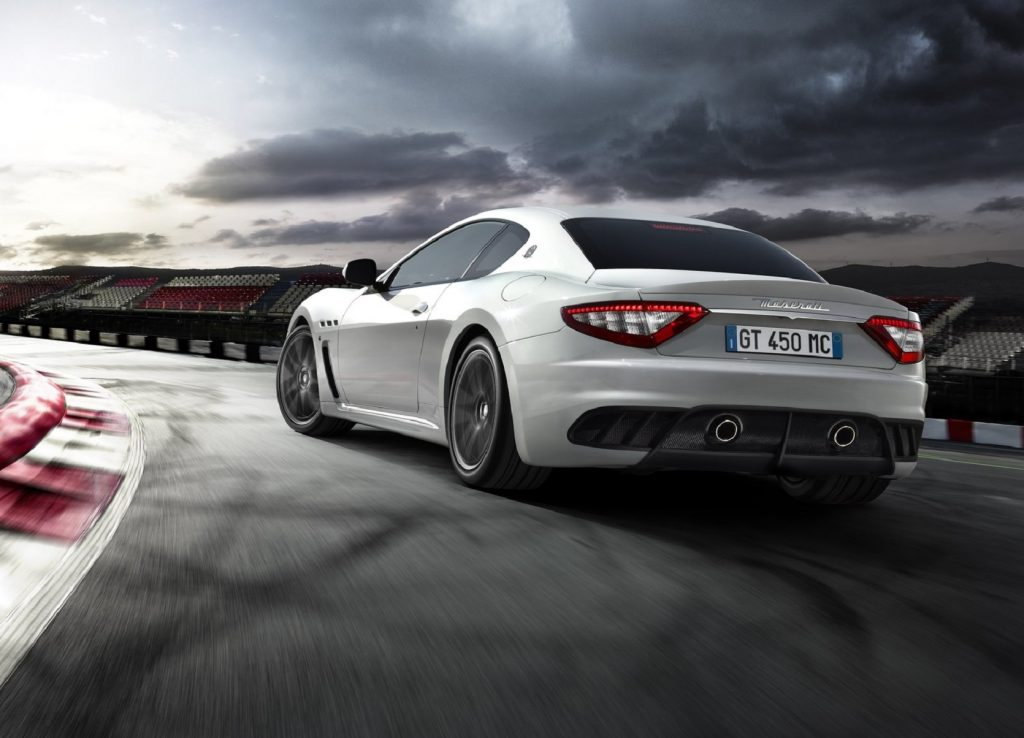 The rear 3/4 view of a white 2012 Maserati GranTurismo MC Stradale on a track