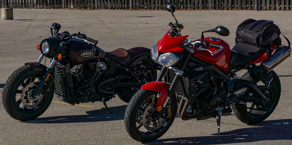 A red 2012 Triumph Street Triple R in front of a maroon 2021 Indian Scout Bobber