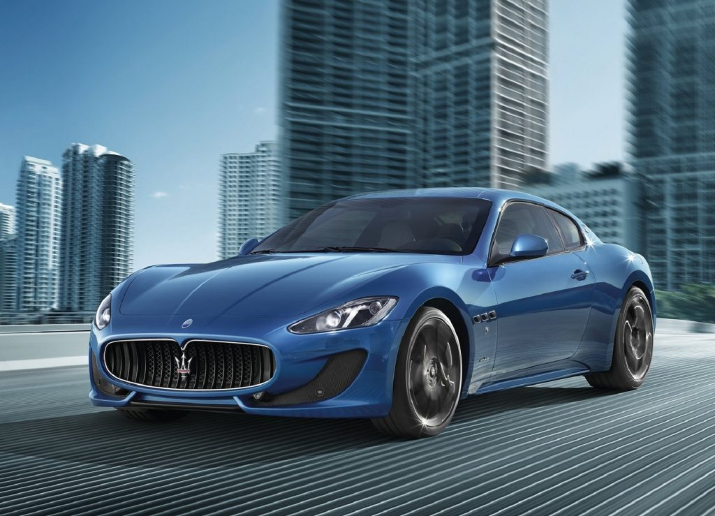 A blue 2013 Maserti GranTurismo Sport drives on a city road