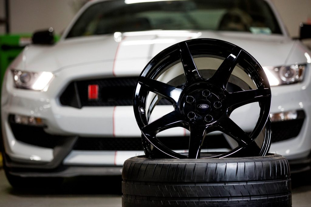 A gray-and-white 2016 Ford Shelby GT350R Mustang behind its black carbon-fiber wheel
