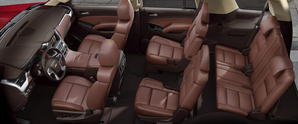 A 2018 Tahoe with brown leather seats.