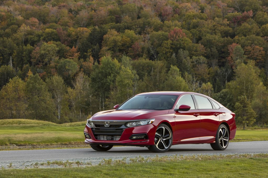 the 2020 Honda Accord in red on a scenic road with a forested landscape in the background