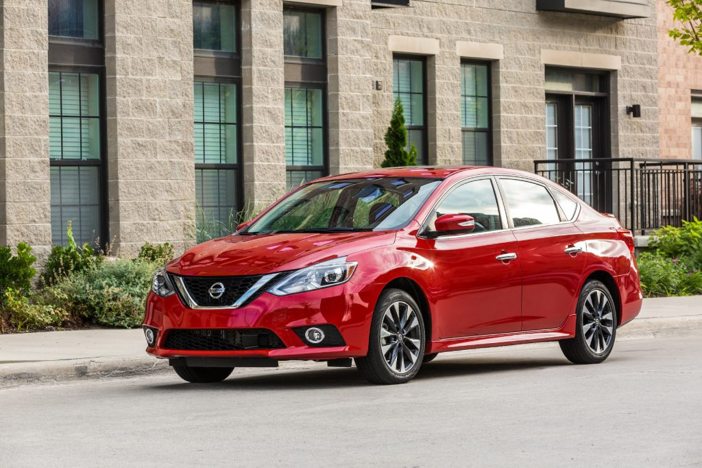 A red 2019 Nissan Sentra driving down a city street