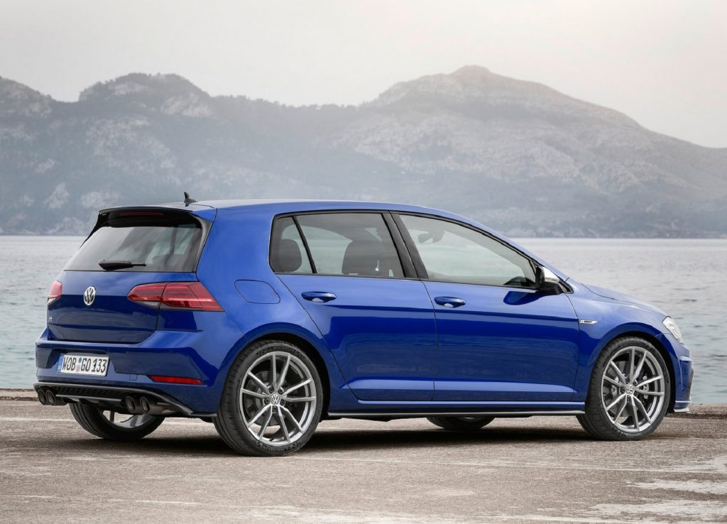The rear 3/4 view of a blue 2019 Volkswagen Golf R by a lake