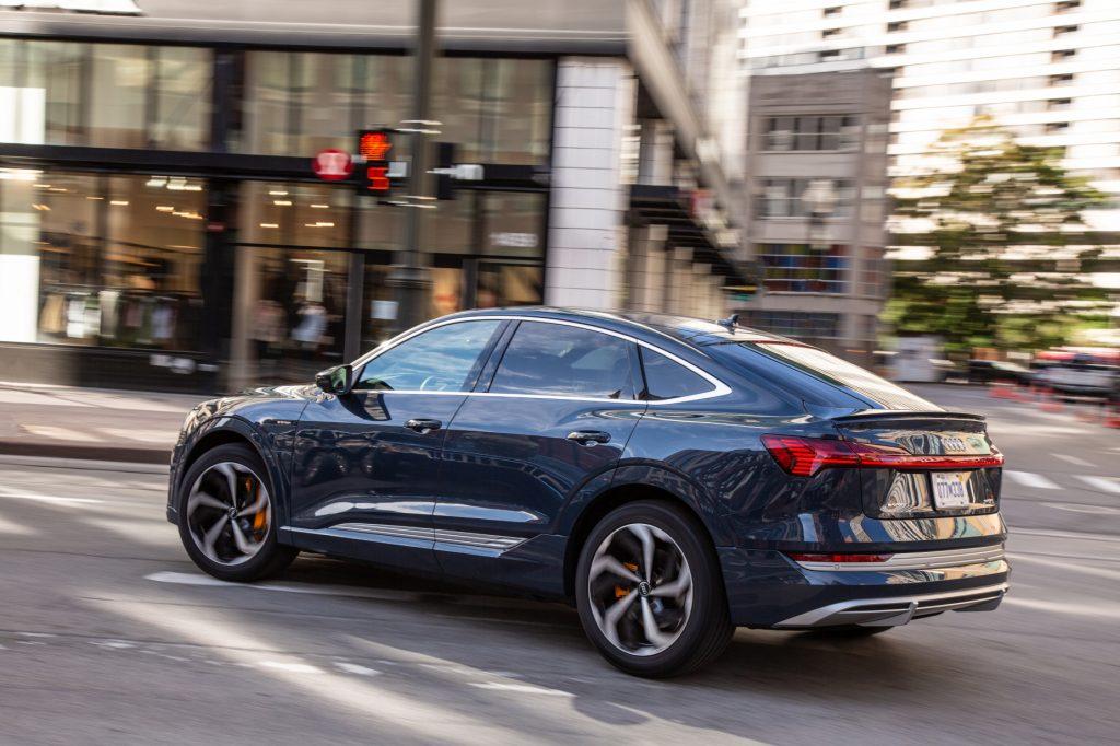 A blue 2020 Audi e-tron driving down a city street
