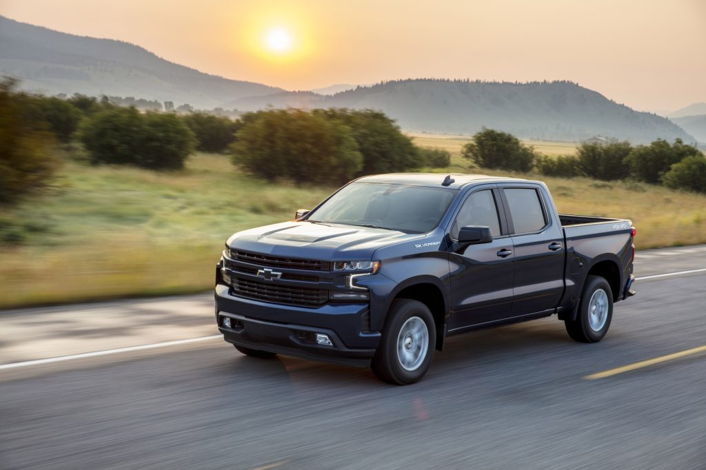 A 2020 Chevy Silverado 1500 driving on the road with trees and the sun in the background