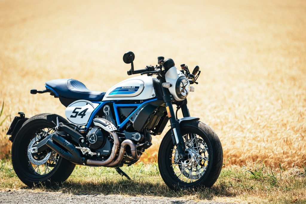 A silver-and-blue 2020 Ducati Scrambler Cafe Racer by a field