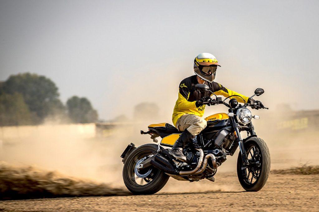 A rider drifts a black-and-yellow 2020 Ducati Scrambler Full Throttle in the desert