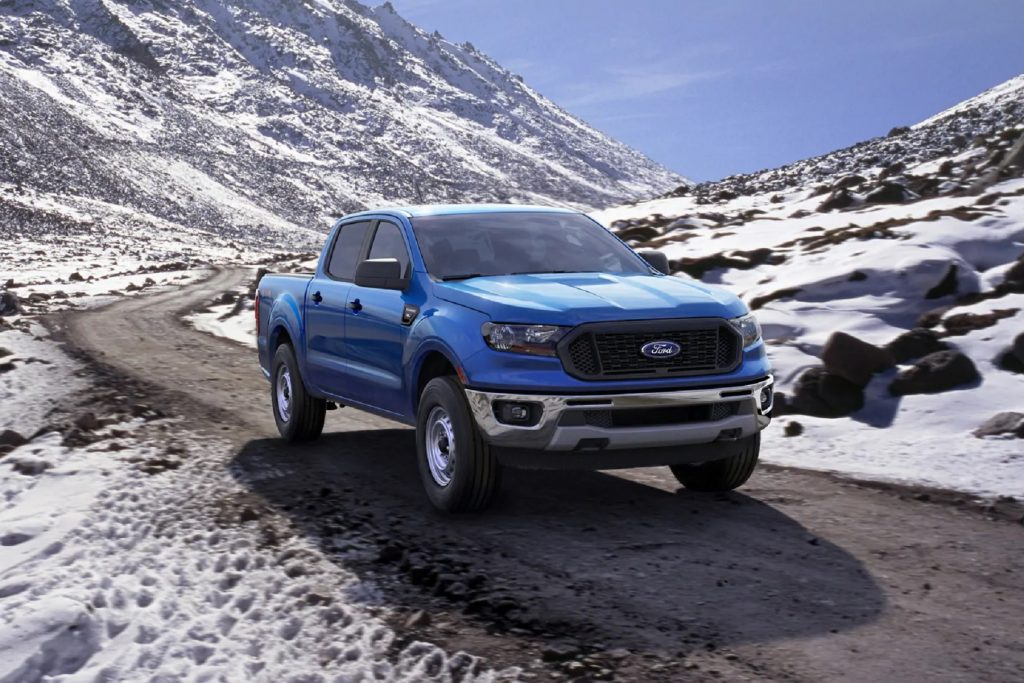 A blue 2020 Ford Ranger XL SuperCrew drives on a paved snowy mountain road