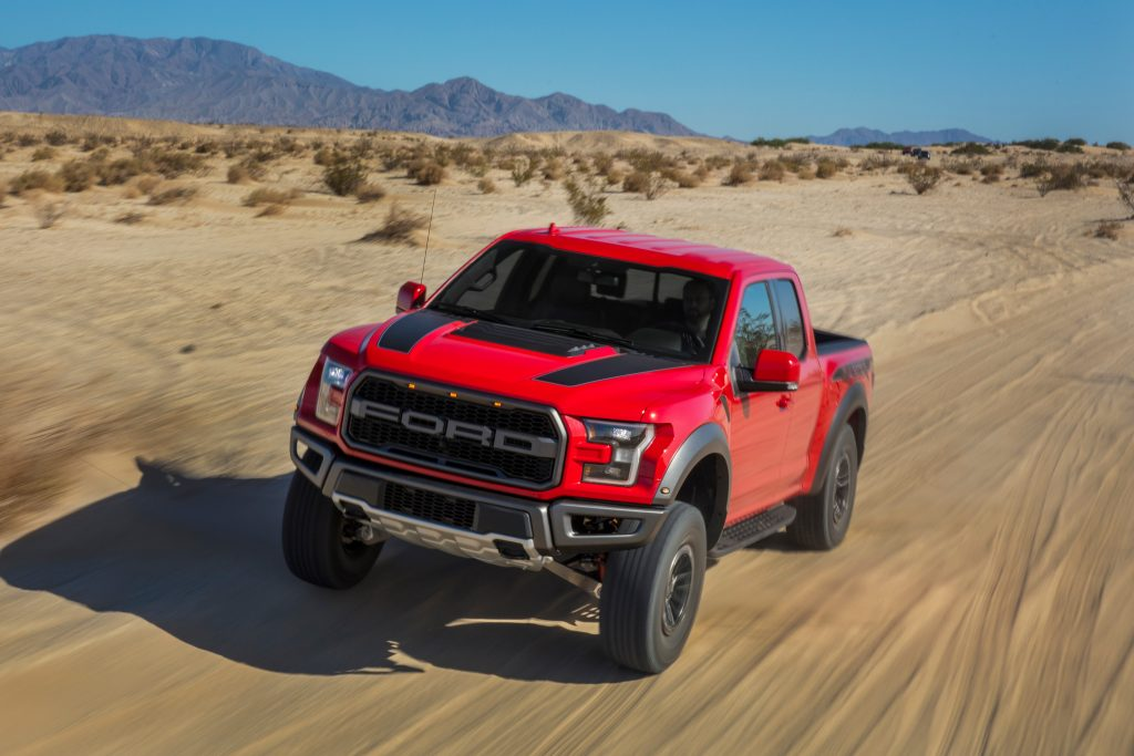 A red 2020 Ford Raptor runs through the desert.