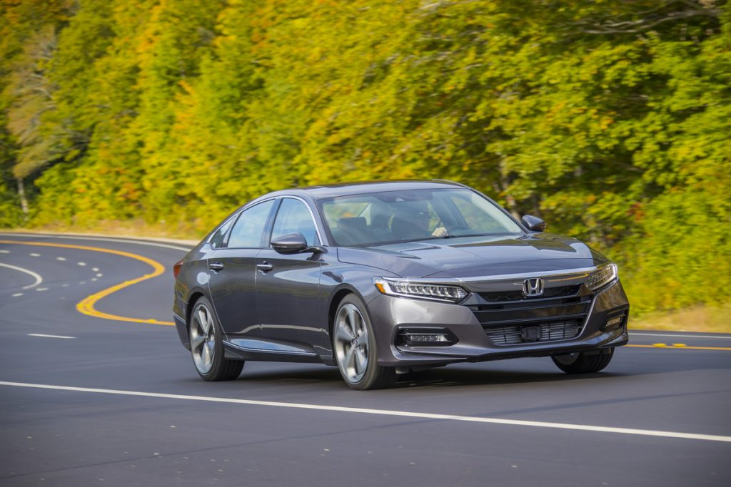 a gray 2020 Honda Accord touring at speed on a scenic road surrounded by forest