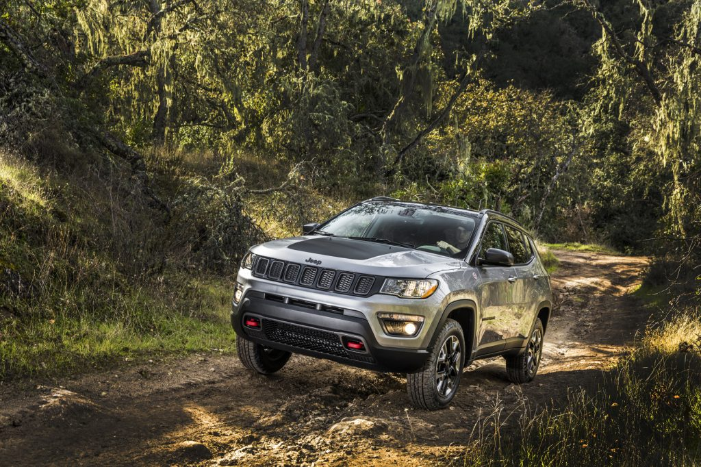 A silver 2020 Jeep Compass driving down a trail in the woods