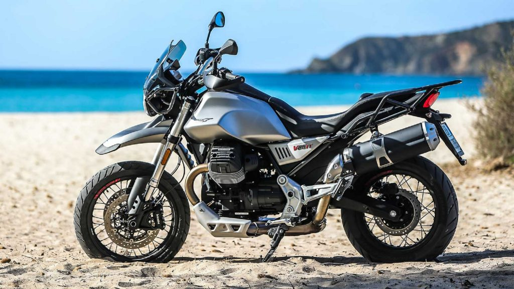 The side view of a silver 2020 Moto Guzzi V85TT on a beach