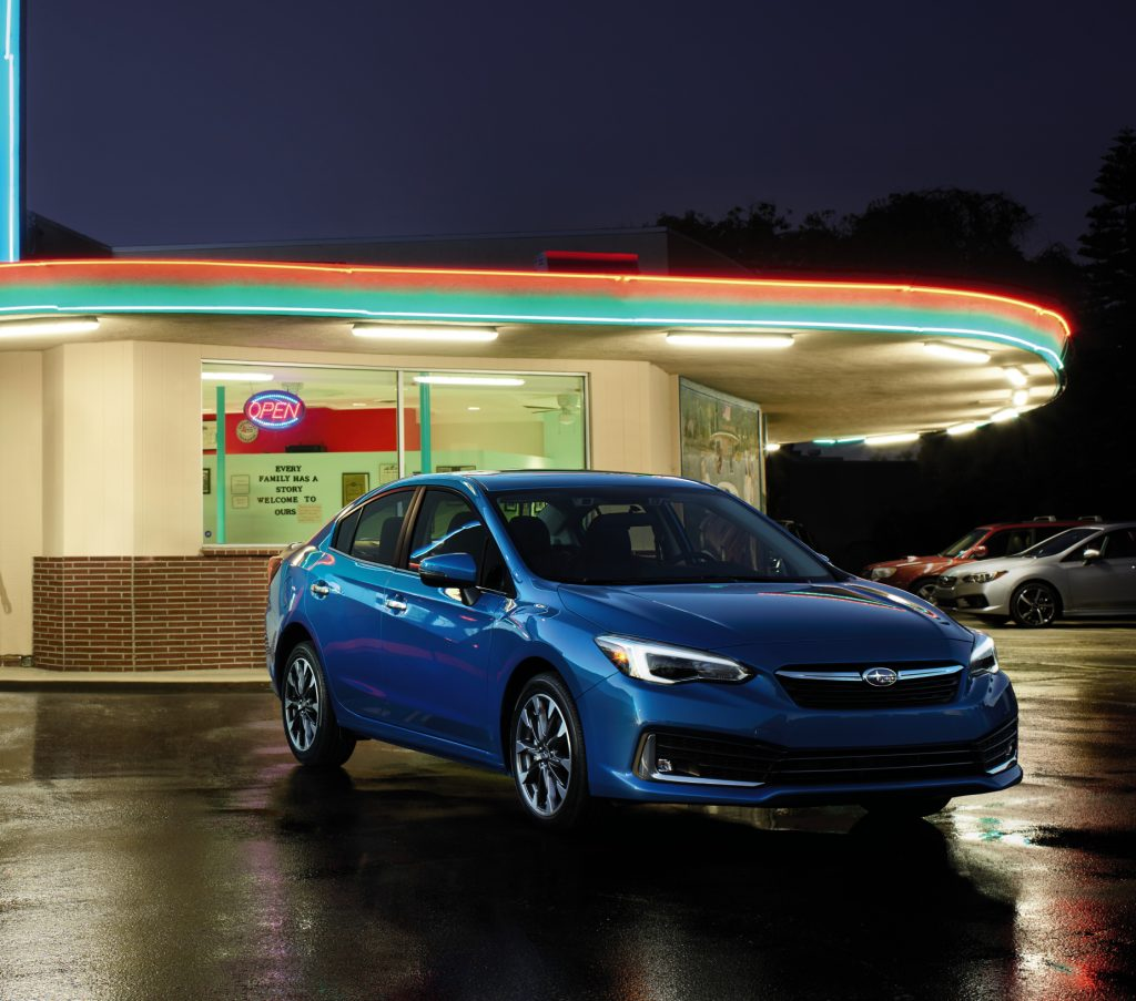 A blue 2020 Subaru Impreza on display in front of a retro diner.