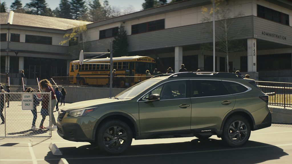 A 2020 Subaru Outback parked in front of a school.