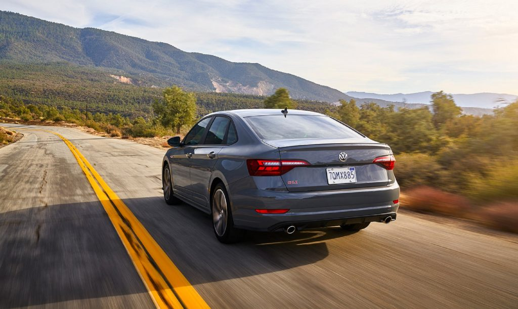 The rear 3/4 view of a gray 2020 Volkswagen Jetta GLI Autobahn driving on a desert plains road