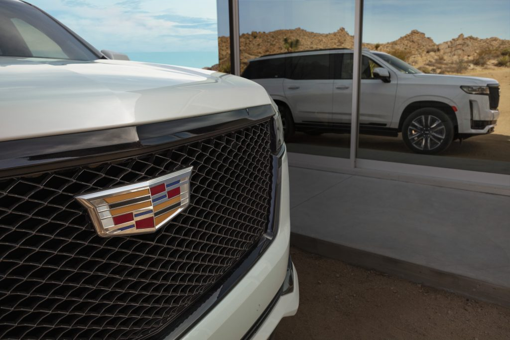 An up close look at the Cadillac logo on the grille of a white 2021 Cadillac Escalade