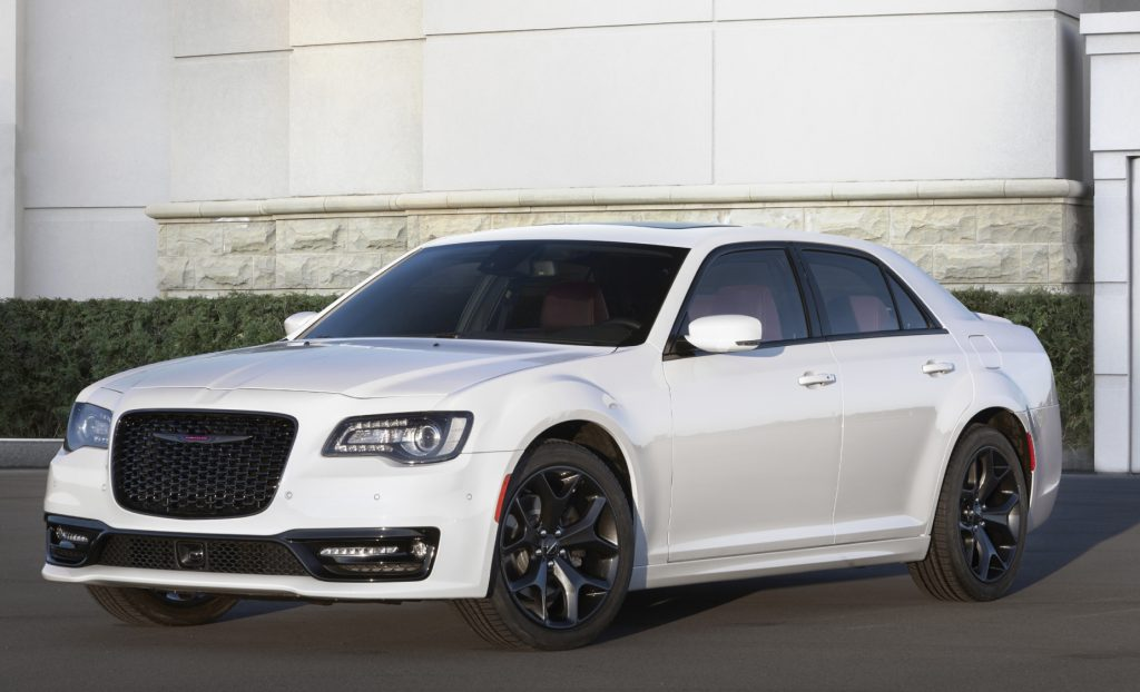 A white 2021 Chrysler 300S parked on display in front of a building