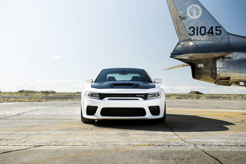 A white and black 2021 Dodge Charger Hellcat Redeye on display next to an airplane