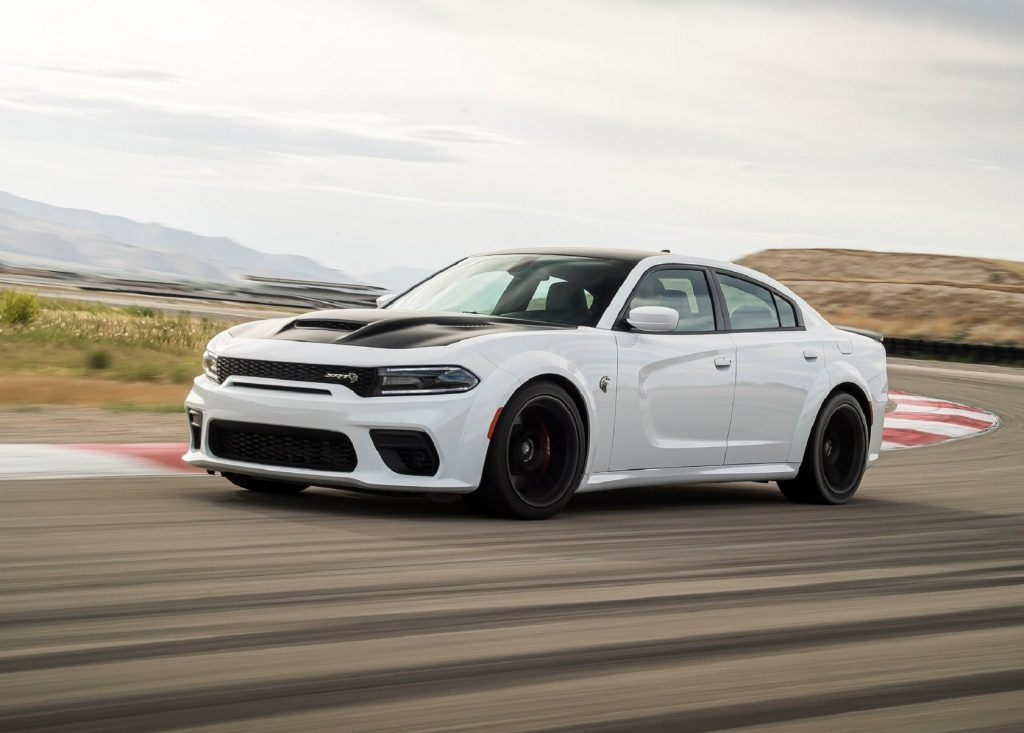 A white 2021 Dodge Charger SRT Hellcat Redeye drives on a racetrack