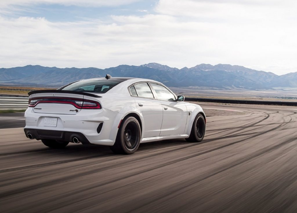 The rear 3/4 view of a white 2021 Dodge Charger SRT Hellcat Redeye on a racetrack