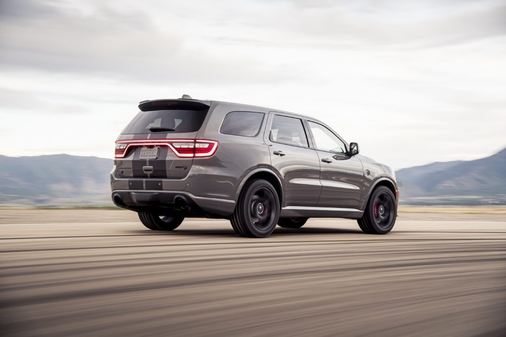 A silver and black 2021 Dodge Durango SRT Hellcat driving away from the camera on a dirt road