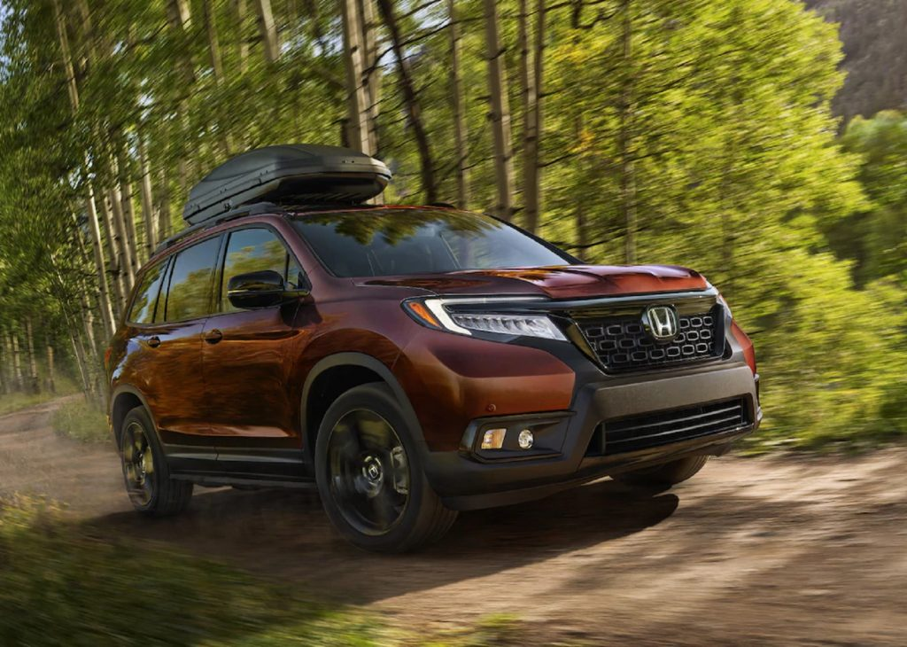 A red 2021 Honda Passport Elite AWD with a roof box drives through a forest