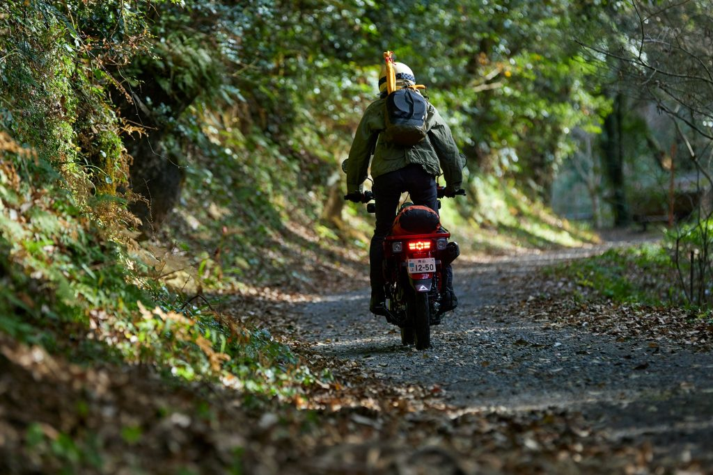 A rider takes a red 2021 Honda Trail 125 on a gravel forest trail