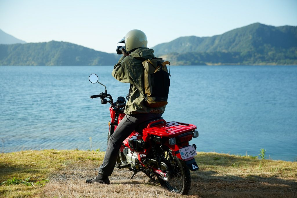 A rider sits on a red 2021 Honda Trail 125 by a lake