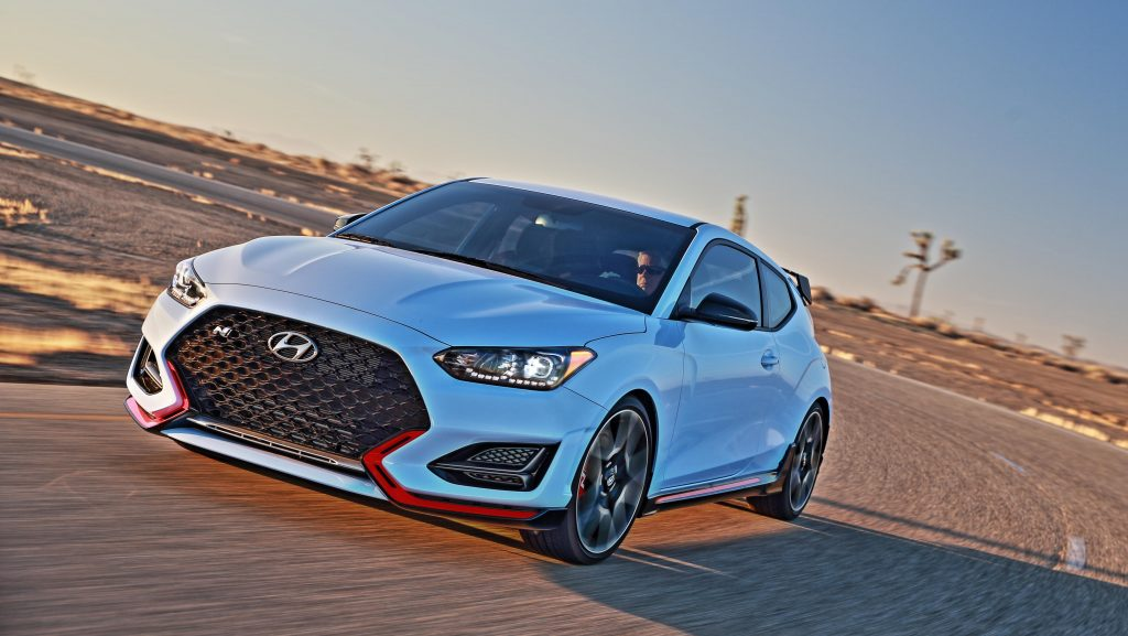 A white 2021 Hyundai Veloster N driving on a race track