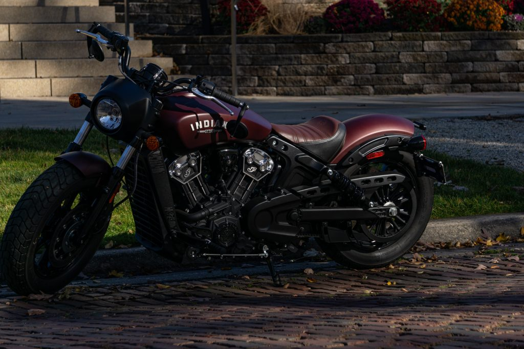 A maroon 2021 Indian Scout Bobber parked on a shady cobblestone road