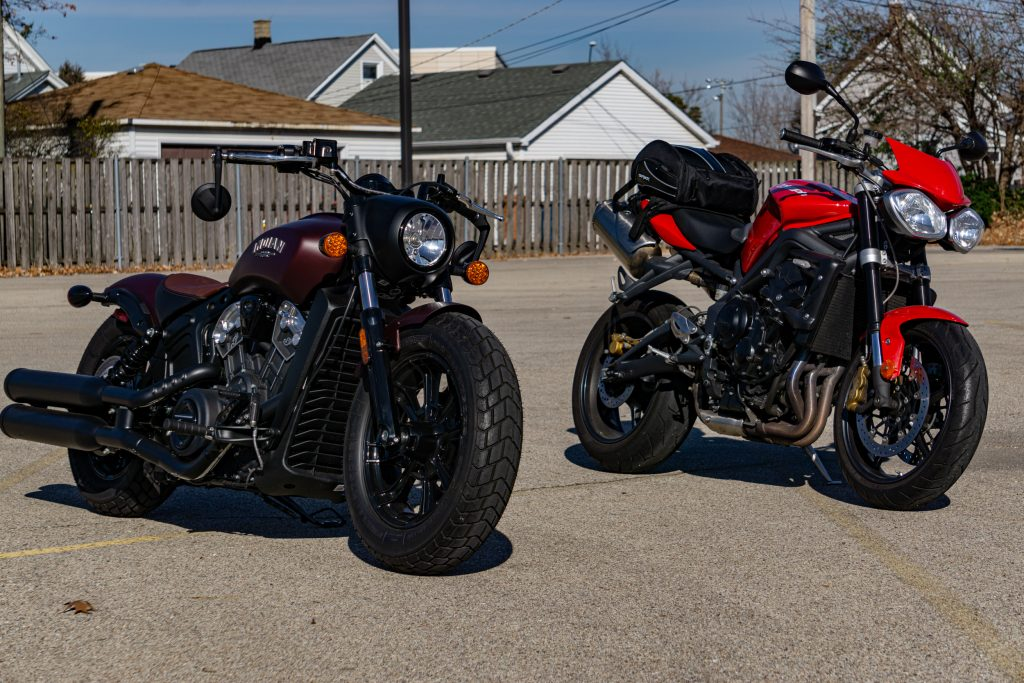 A maroon 2021 Indian Scout Bobber next to a red 2012 Triumph Street Triple R