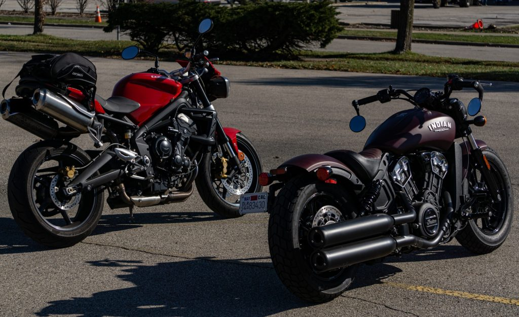 The rear 3/4 view of a red 2012 Triumph Street Triple R next to a maroon 2021 Indian Scout Bobber