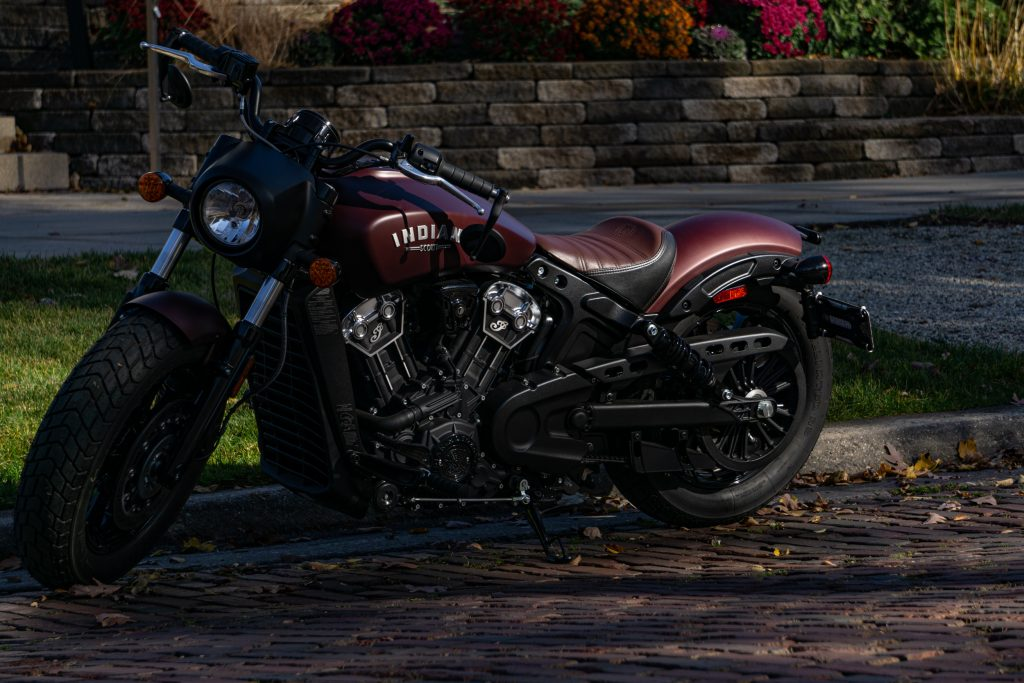 The front 3/4 view of a maroon 2021 Indian Scout Bobber on a shady street