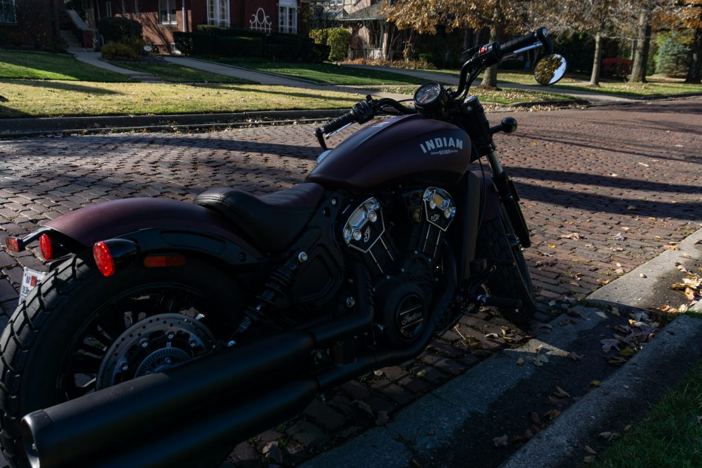 The rear 3/4 view of a maroon 2021 Indian Scout Bobber on a cobblestone street
