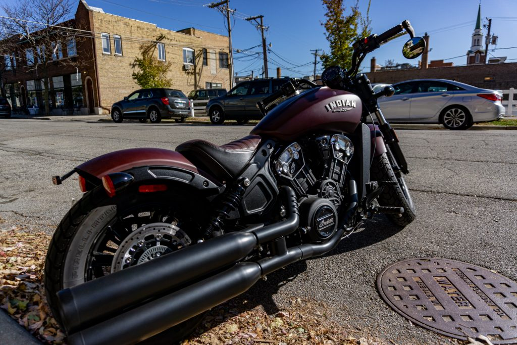 The rear 3/4 view of a maroon 2021 Indian Scout Bobber on the street