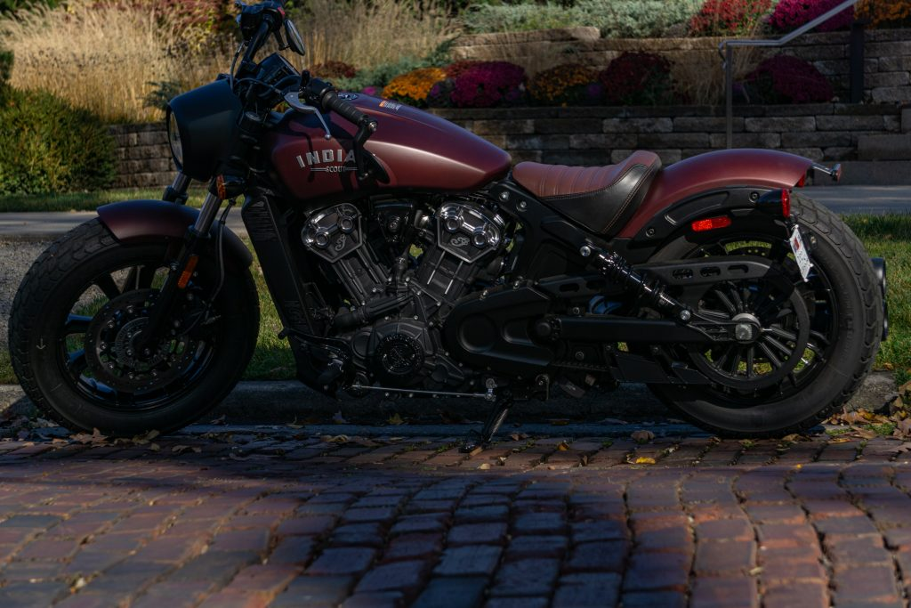 The side view of a maroon 2021 Indian Scout Bobber on a cobblestone street
